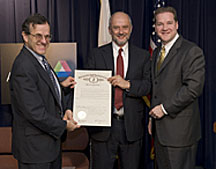 Illinois Department of Commerce and Economic Opportunity Director Jack Lavin (right) presents Argonne Director Robert Rosner (left) and Fermilab Director Pier Oddone with the Particle Accelerator Day proclamation.