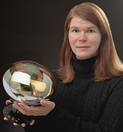 Columbia University's Janet Conrad holds one of the 1520 light sensors installed inside the MiniBooNE detector.