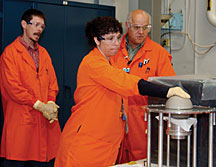 With her gloved hand on a uranium test assembly, Barbara Kr�gfuss of Y-12 participates in a nuclear criticality training exercise with LLNL certified fissile material handler Nolan Lomba (right) as Mark Lee of the DOE Livermore Site Office looks on.